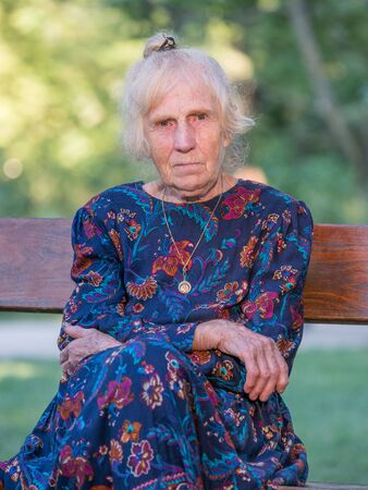 An elegantly dressed, elderly woman is sitting on a park benchis sitting on a park bench. Poland.