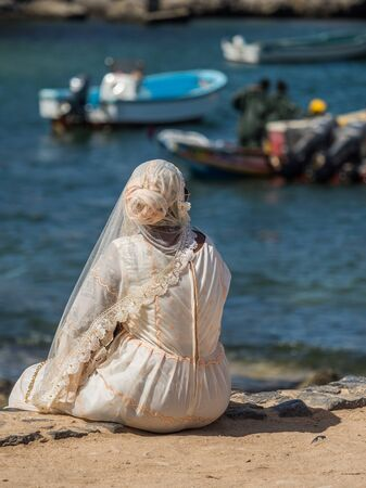 View of Senegalese woman in a white wedding dress sitting by  the ocean on  island of Goree, Stok Fotoğraf