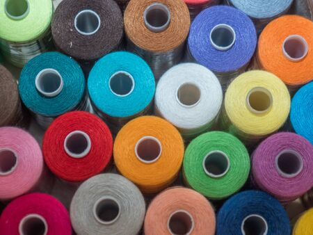 A lot of sewing colored thread. Thread reels. Colorful threads in the box. Texture of sewing accessories