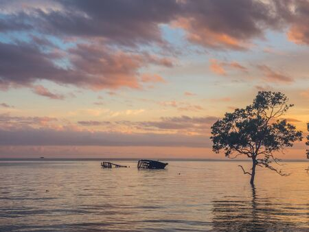 View for the tropical sunset with silhouettes of  treee and boat during the  high tide on Saram Sea. Kaimana, Birds Head Peninsula,  West Papua, Indonesia, Asia. Stok Fotoğraf