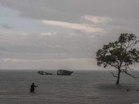 View of the silhouettes of a tree, a destroyed boat and a fisherman during high tide on the Saram Sea. Rainy weather.  Kaimana, Bird's Head Peninsula, West Papua, Indonesia, Asia. Stok Fotoğraf - 137488775