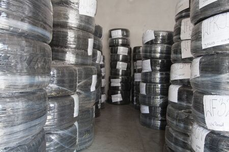 Stacks of used tires wrapped with foil are in stock. Black rubber tire, part of the vehicle, spare part. Stok Fotoğraf - 137489648