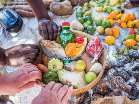 Hands of a white and black woman doing shopping together at the local market Stok Fotoğraf - 137495634