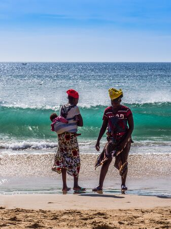 Dakar, Senegal - February 3, 2019: Senegalese women with children on their back on a sandy beach in Dakar. Africa.