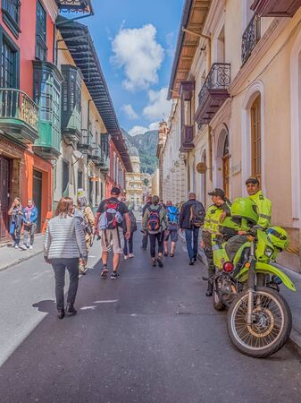 Bogota, Colombia - September 12, 2019: Street of Bogota with colonial colorful houses, crowd of the people, police man with motorcycle and mountain view in the background, La Candelaria district.