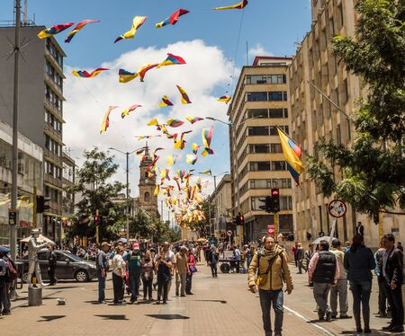 Bogota, Colombia - September 12, 2019: Street of Bogota with colombian flags, crowd of people and view of cathedral in the background , La Candelaria district. Editöryel