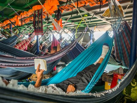 Amazon River, Peru - Decemberr 9, 2019: Man praying while laying on colorful hammocks on the cargo boat. South America. Amazonia