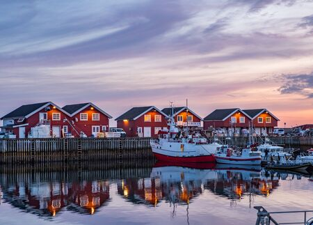 Moloen, Bodo, Norway - August 18, 2019:  View of the marina. fishing boats and typical wooden nordic houses with reflection in the water after sunset Nordland. Europe. Gate to Lofoten