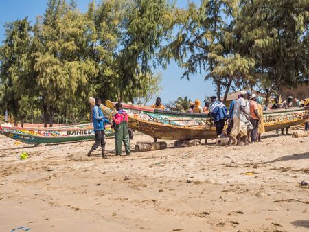 Nianing, Senegal - January 2, 2019: Fishermen collecting fish from colored wooden fisher boat standing on the beach. Africa