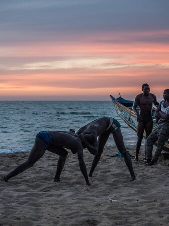 Nianing, Senegal - January 24, 2019: Unidentified silhouettes of wrestlers trained on the beach during the sunset. Senegalese wrestling is a national sport in Senegal. Africa.