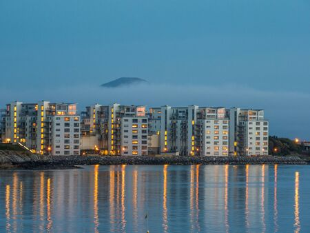 Bodo, Norway - August 18, 2019: Night view of blocks of flats in centrum of Bodo city on bank of fjord with reflection in the water. Mountain covered with a cloud in the background. Nordland Europe. Gate to Lofoten Editöryel