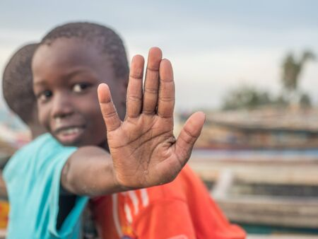 Senegal, Africa - January, 24, 2019: Opened hands of a black boy. Colorful Senegalese boats in the background. Senegal. Africa.