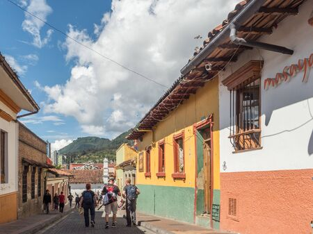 Bogota, Colombia - September 12, 2019: Street of Bogota with colonial colorful houses and mountain view in the background, La Candelaria district.