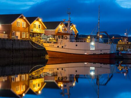 Moloen, Bodo, Norway - August 18, 2019:  View of the marina. fishing boats and typical wooden nordic houses with reflection in the water during the night. Nordland. Europe. Gate to Lofoten