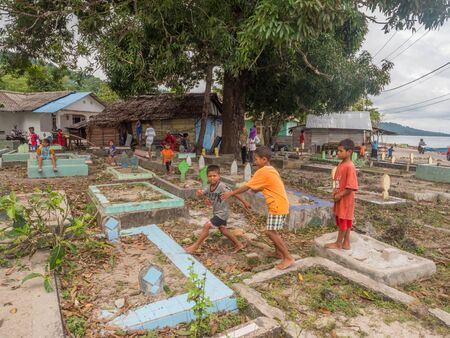 Ambon, Indonesia - February 11, 2018: Children on local muslim cemetery in the small town on Ambon Island, Maluku