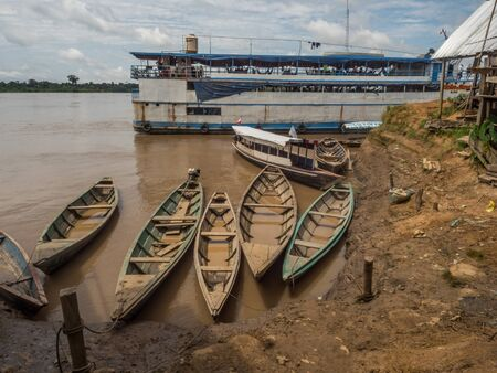 Santa Rosa, Peru - December 12, 2019: Wooden boats  and cargo boot in  the port of Amazon river. South America. Amazon River.  Tres fronteras. Rain Forest of Amazonia. Editöryel