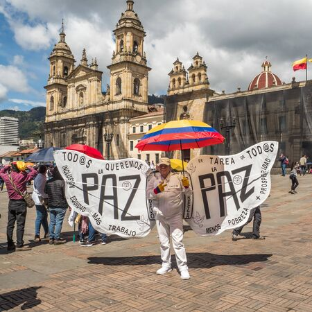 Bogota, Colombia - December 12, 2019:  A Colombian in costume with angel wings demonstrates on the main square. The inscription on the wings reads: We all want less poverty, more prosperity and work, job for everyone, we all want peace,