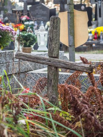 A small wooden cross on a forgotten grave in a cemetery in Poland