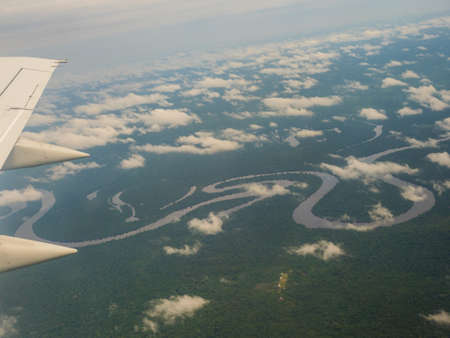View from airplane window. Wing of an airplane flying above the clouds over Amazon River. Top View of Amazon rainforest. Peru, Brazil. Colombia. Zdjęcie Seryjne