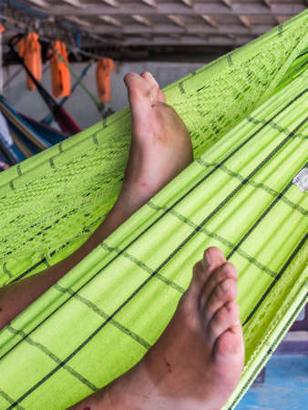 Close-up for legs on the green hammock on the cargo boat. South America. Amazonia, trail from Santa Rosa to Iquitos