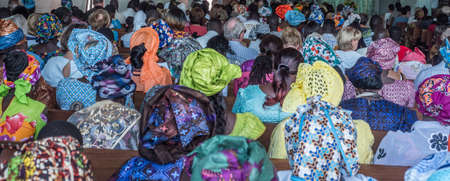 Senegal, Africa - January 2019: African people in colorful clothes (boubou) during a mass at a Catholic church in West Africa Sajtókép