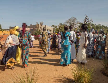 Senegal, Africa - January 2019: African people in colorful clothes (boubou) meet after the mass at a Catholic church in West Africa