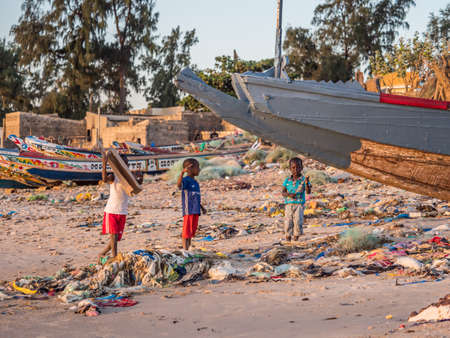 Senegal, Africa - January 26, 2019: Chidren playing on the beach with plenty of waste. Pollution concept. Colorful fisher boats in the background. Senegal. Africa.