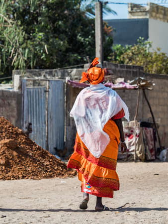 Senegal, Africa - Jan, 2019: Senegalese woman in a traditional costume called 'boubou' walking along the street.