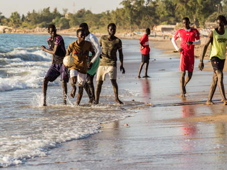 Senegal, Africa - January 26, 2019: Young african boys are play football on the beach. Senegal. Africa.