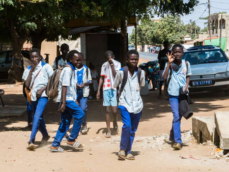 Nianing, Senegal, Africa - January 2019: A group of schoolchildren in blue uniforms on the street of small town in Senegal. Africa.