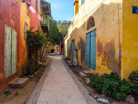 Everyday life and street with a cobblestone road between colorful houses on the island of Goree. Gorée. Dakar, Senegal. Africa.