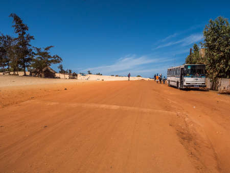 Senegal, Africa - Feb 02, 2019: Old bus the road with red and white sand at the end of the past Paris-Dakar route 免版税图像