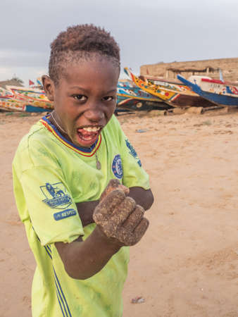 Senegal, Africa - January 24, 2019: Portrait of a black boy with a funny face. Colorful Senegalese boats in the background. Senegal Africa. Sajtókép
