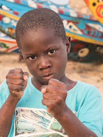 Senegal, Africa - January 24, 2019: Portrait of a black boy with a funny face. Colorful Senegalese boats in the background. Senegal Africa. 新闻类图片