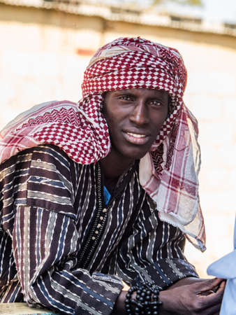 Senegal, Africa - January 25, 2019: Portrait of African man wearing a keffiyeh on his head (also known as a ghutrah, shemagh, ḥaṭṭah, mashadah, chafiye, dastmal yazdi or cemedanî)