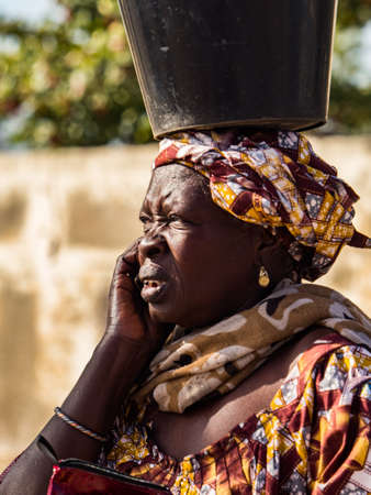 Joal-Fadiouth, Africa - Jan, 2019: Senegalese woman with a bucket on her head. The Thiès region at the end of the Petite Côte of Senegal 免版税图像 - 158643914