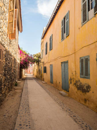 Goree, Senegal- February 2, 2019: Everyday life and street with a cobblestone road between colorful houses on the island of Goree. Gorée. Dakar, Senegal. Africa.