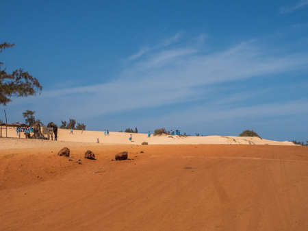 Senegal, Africa - Feb 02, 2019: Road with red and white sand at the end of the past Paris-Dakar route 免版税图像