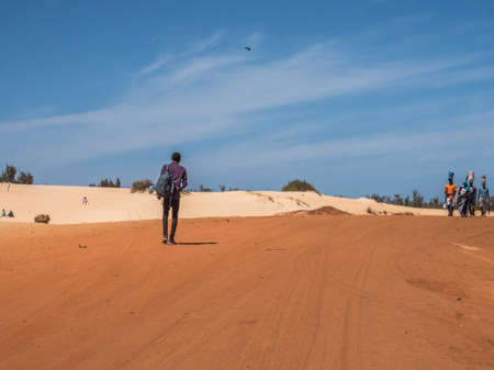 Senegal, Africa - Feb 02, 2019: Black man on road with red and white sand at the end of the past Paris-Dakar route 新闻类图片