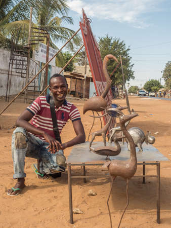 Senegal, Africa - January 24, 2019: Happy man from Senegal shows his handicrafts made of metal on the street in the small village in the Senegal 新闻类图片