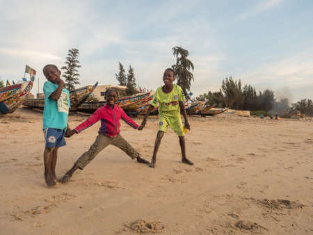 Senegal, Africa - January 2019: Portrait of a black happy boys on the sandy beach next to the ocean. Colorful Senegalese boats in the background. Senegal Africa.