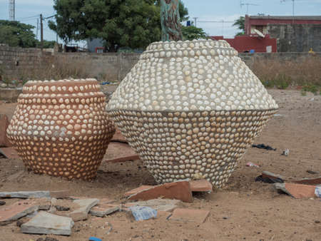 Two huge vases covered with small shells stand on a street in Senegal, West Africa.
