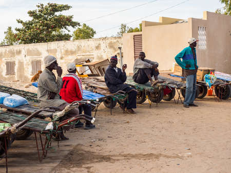 Joal-Fadiouth, Senegal - January 24, 2019: African men waiting with the carts next to island Joal-Fadiouth. Town and commune is in the Thiès Region at the end of the Petite Côte of Senegal. Africa.
