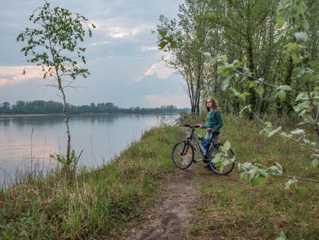 Józefów, Poland- April 29, 2019: A woman on a bike on the path along the Vistula River. Świderskie Island Reserve. Masovian district. Poland, Europe.