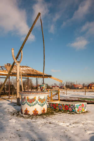 Zalipie, Poland - May 20, 2017: Hand-painted well and a metal bucket in a colorful village - Zalipie, an open-air museum in which all buildings and objects are decorated with a traditional floral motif. Winter time. Eastern Europe.