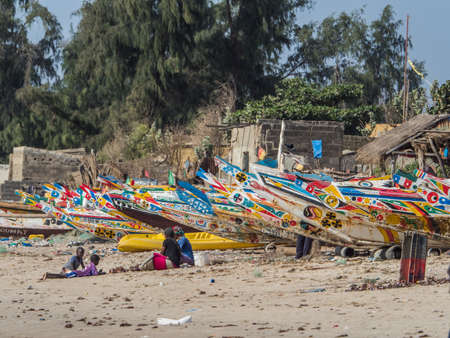 Nianing, Senegal - January 24, 2019: African family sitting close to the colorful wooden fishing boats standing on the sandy beach in Senegal. Africa