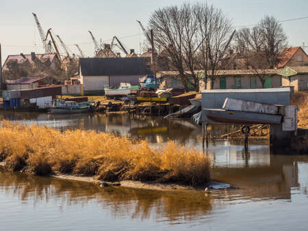 Klaipeda, Lithuania - April 6, 2018: Poor district in the suburbs of the city with houses built on small boats on the bank of the canal, city of slums, shanty town. Eastern Europe