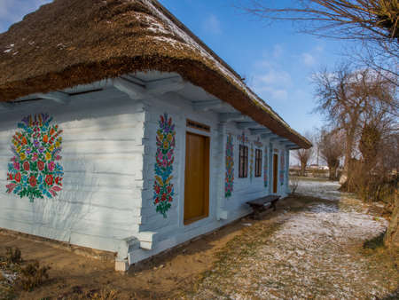 Zalipie, Poland - January 06, 2017: House with blue frames and colorful flowers painted on walls in the village of Zalipie 新闻类图片