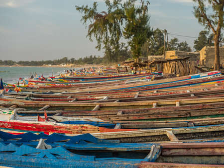 Nianing, Senegal - January 24, 2019: Colorful wooden fisher boats standing on the sandy beach in Senegal. africa 新闻类图片