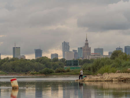 Warsaw, Poland - Aug 25 2018: Skyscrapers, Fat KaÅ›ka and Palace of Culture and Science in the center of Warsaw seen from the deck of a boat sailing on the Vistula. East Europe